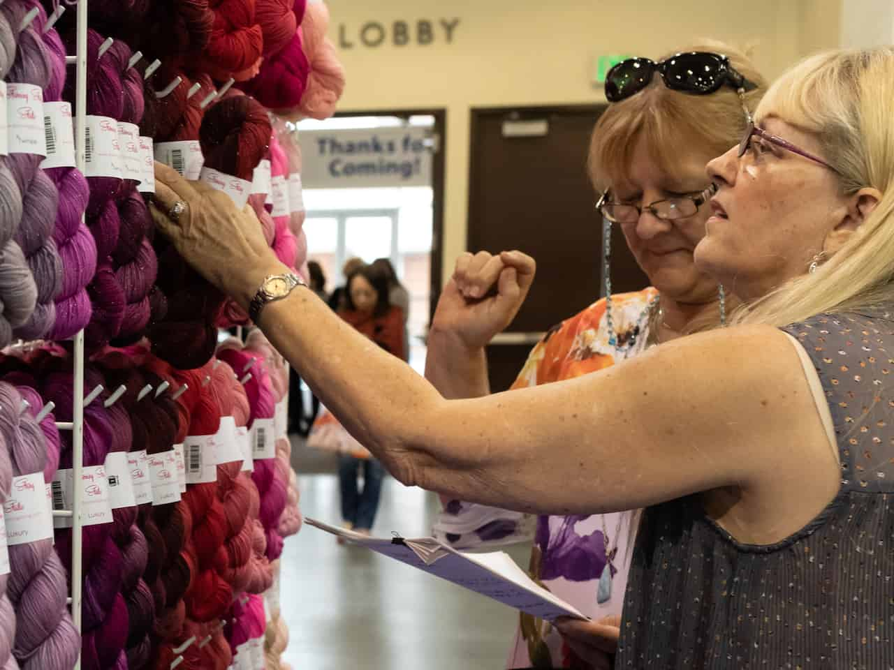 Two women looking at skeins of yarn